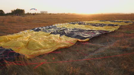 hang gliding : Parachute lying on the ground in the sunset rays of the sun on the airfield