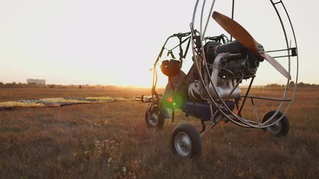 padák : Motor paraglider stands at the airport in the rays of sunset sunlight. The camera moves along the orbit