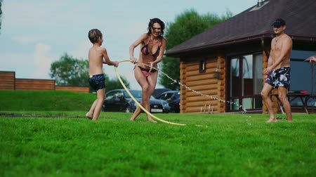 water sprayer : Family in the backyard of a country house in the summer relax playing with water and hosing