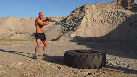 functionality : Bald man strongman hits a hammer on a huge wheel in the sandy mountains in slow motion. strength and endurance training for wrestlers. Stock Footage