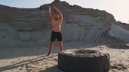 functionality : Muscle athlete strongman man hits a hammer on a huge wheel in the sandy mountains in slow motion at sunset. The dust from the wheels rises.