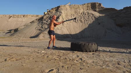 functionality : Muscle athlete strongman man hits a hammer on a huge wheel in the sandy mountains in slow motion. strength and endurance training for wrestlers
