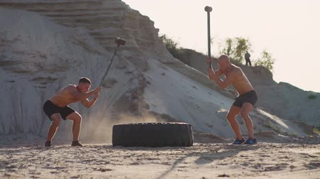 functionality : Two male athletes training together hit the wheel with a hammer at sunset in the mountains on the sand. Endurance training
