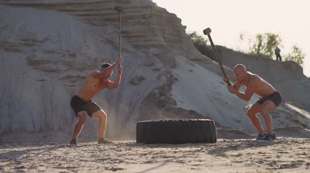 functionality : Two powerful male athletes training together hit the wheel with a hammer at sunset in the desert. Endurance training Stock Footage