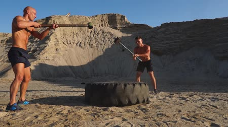 ağır çekimli : Two powerful male athletes training together hit the wheel with a hammer at sunset in the desert. Endurance training Stok Video