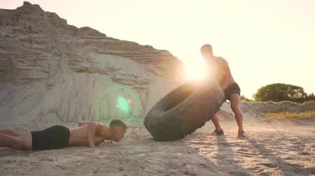 мышечной построить : Two muscular open-chested athletes train in active mode on the beach doing push-UPS and pushing a huge wheel against a sandy mountain at sunset Стоковые видеозаписи