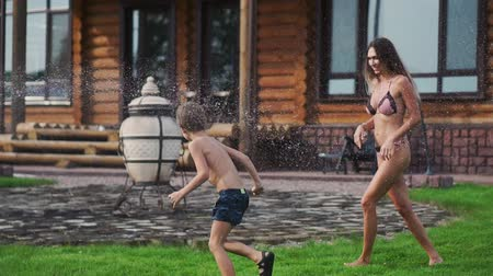 шланг : Mother and father playing with children on the lawn of the house pouring water from a hose Стоковые видеозаписи