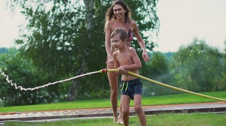 шланг : Mom and son playing on the lawn pouring water laughing and having fun on the Playground with a lawn on the background of his house near the lake