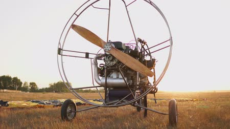 padák : The motor paraglider stands in the field at sunset with a wooden propeller, and the pilot lays out the parachute and aligns the slings. flight preparation Dostupné videozáznamy