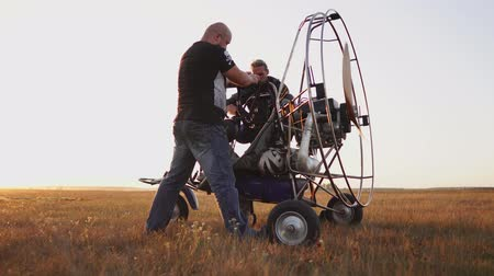padák : Motor paraglider stands in the field at sunset with a wooden propeller, two pilots warm up the engine before the flight Dostupné videozáznamy