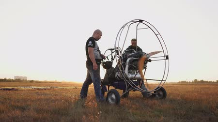 летчик : Motor paraglider stands in a field at sunset with a wooden propeller, two pilots warm up the engine before the flight. A test run of all systems
