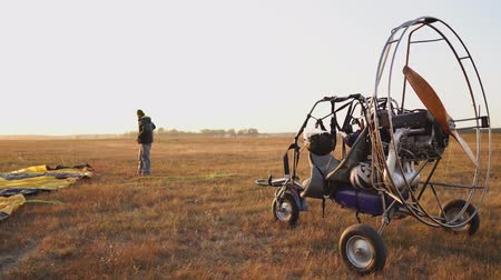 padák : The motor paraglider stands in the field at sunset with a wooden propeller, and the pilot lays out the parachute and aligns the slings
