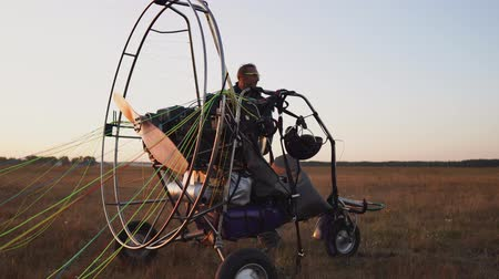 padák : A man pilot of a motor paraglider attaches the parachute to the body of the paraglider preparing for flight and checking equipment