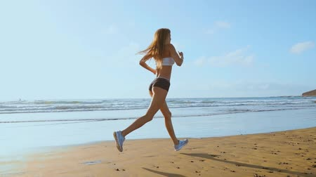 бегун трусцой : Beautiful woman in sports shorts and t-shirt running on the beach with white sand and blue ocean water on the island in slow motion. Waves and sand hills on the back won Стоковые видеозаписи