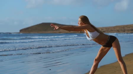 braços levantados : Woman stretching legs and hamstrings doing Standing Forward Bend Yoga stretch pose on beach. Fitness woman relaxing and practising sport and yoga on.