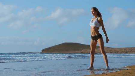 squat : Sportswoman Wearing Sportswear Doing Squats Exercise Outdoors. Fitness Female Working Out on the Beach at Sunset. Athletic Young Woman is Engaged in Outdoor Sports.