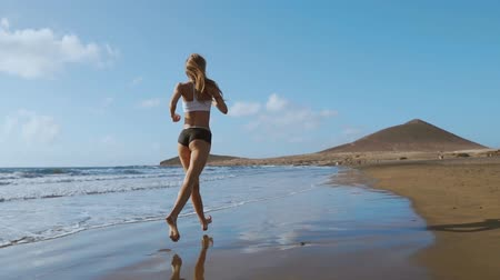 cardio workout : Fitness runner woman running on beach listening to music motivation with phone case sport armband strap. Sporty athlete training cardio barefoot with determination under summer sun. Stock Footage