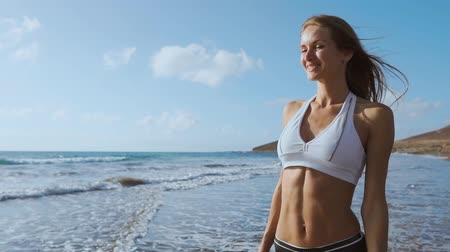 esportivo : Young woman walking on beach Stock Footage