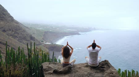 nápadný : A man and a woman sitting on top of a mountain looking at the ocean sitting on a stone meditating raising their hands up and performing a relaxing breath. Canary islands Dostupné videozáznamy