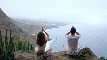 north bay : A man and a woman sitting on top of a mountain looking at the ocean sitting on a stone meditating raising their hands up and performing a relaxing breath. Canary islands Stock Footage