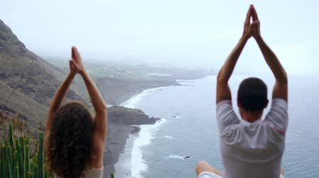 marcante : A man and a woman sitting on top of a mountain looking at the ocean sitting on a stone meditating raising their hands up and performing a relaxing breath. Canary islands Vídeos