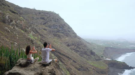 Ванкувер : A man and a woman sitting on top of a mountain looking at the ocean sitting on a stone meditating raising their hands up and performing a relaxing breath. Canary islands Стоковые видеозаписи
