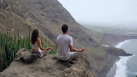 duygusallık : A man and a woman sitting on top of a mountain looking at the ocean sitting on a stone meditating in a Lotus position. The view from the back. Canary islands