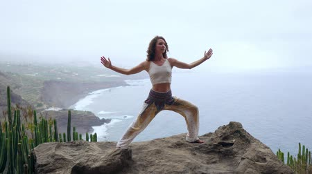 realizar : Woman meditating in yoga warrior pose at the ocean, beach and rock mountains. Motivation and inspirational fit and exercising. Healthy lifestyle outdoors in nature, fitness concept. Vídeos