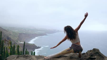 trecho : A woman sitting on the edge of a cliff in a pose war overlooking the ocean raise her hands up and inhale the sea air while doing yoga