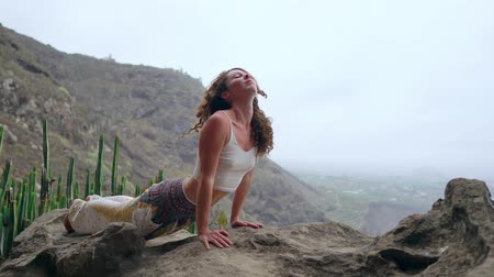アーサナ : Young Caucasian woman performing upward facing dog pose outdoors
