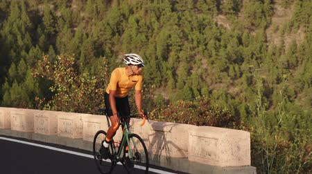 çakıl : A man on a sports road bike rides on the road located high in the mountains Stok Video