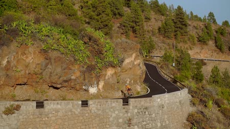düzgün vücutlu : Tracking video shot of a male cyclist climbing up a mountain road. Man doing cycling training on a hilly highway road on a sunny day.