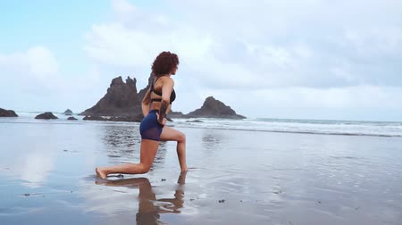 warming up : the girl does a warm-up before doing sports early in the morning on the seashore. A girl of athletic build with a dry muscle mass. Stock Footage