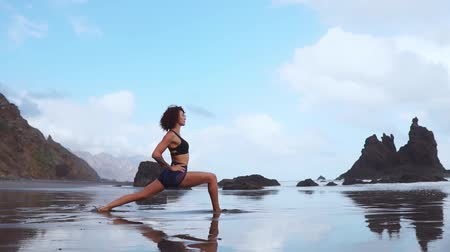 paz mental : Happy young woman practicing yoga on the beach at sunset. Healthy active lifestyle concept. Slow motion Archivo de Video