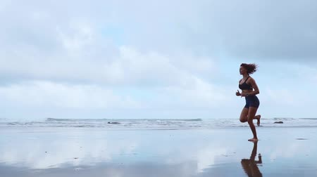závazek : Running woman outdoors beach run. Atlantic ocean
