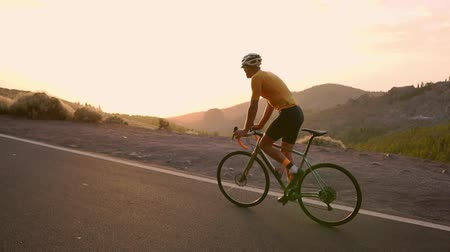 рекреационных преследования : A professional cyclist in a helmet and sports equipment rides on a mountain highway at sunset in slow motion. Steadicam
