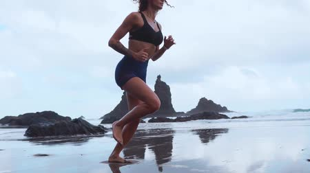 só as mulheres jovens : Girl running on black volcanic sand on the ocean in slow motion