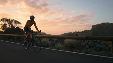 рекреационных преследования : Man bicyclist in yellow t-shirt rides a mountain bike at sunset on the highway