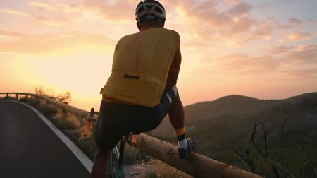 рекреационных преследования : Man cyclist in a yellow t-shirt in the mountains watching the sunset. Resting after a workout, iron man Стоковые видеозаписи