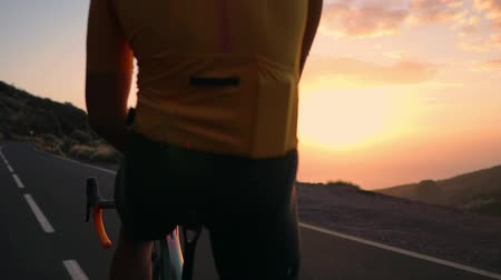 рекреационных преследования : Man cyclist in a yellow t-shirt in the mountains watching the sunset. Resting after a workout, iron man. The view from the back Стоковые видеозаписи