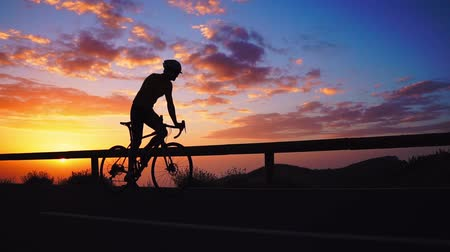 bisikletçi : Silhouette of a cyclist at sunset in the mountains