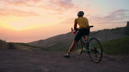 recreational pursuit : A tourist on a Bicycle admires the sunset from the top of the mountain Stock Footage