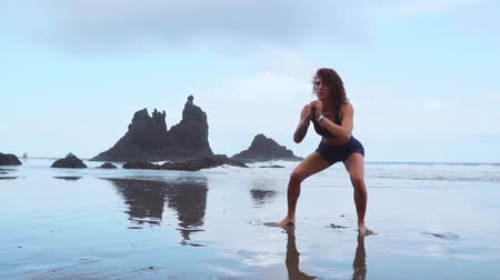 squatting : Fit woman training legs with hiit workout jumping squats exercises. Fitness training doing cardio exercise on summer ocean white sand beach doing explosive jumps and burpees to activate the glutes. Stock Footage