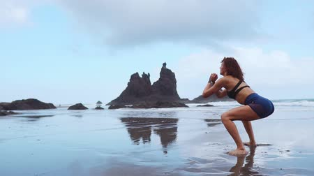 stehno : Girl jumping burpee workout on the black sand beach near the Atlantic ocean with mountains in the background