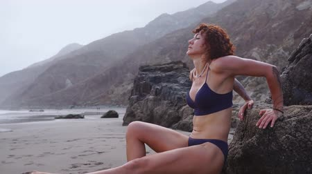 plage : Woman doing push-UPS on a rock on the beach near the ocean. Fitness young woman doing push ups on beach Stock Footage