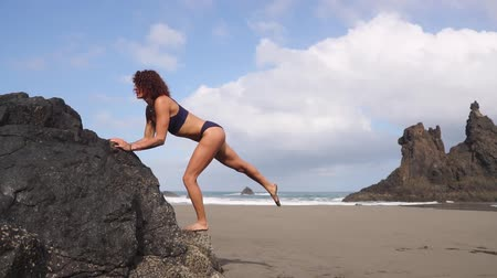 plage : A woman performs squats and lunges from a rock on a beach near the ocean