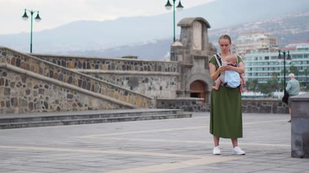 bridge man made structure : A young woman with a baby in a sling travels to Europe. Standing on the square near the ocean takes on the phone attractions and is online broadcast for your blog