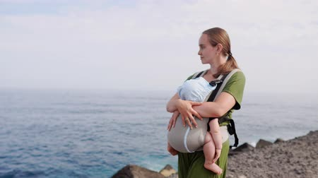 doorkijkjes : Baby and mother on sea at summer day. Happy family walking on nature outdoors. Child in a carrier backpack. Woman and her baby on coastline ocean on the island of Tenerife, Spain. Travel Europe