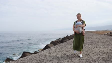 vergezichten : Baby and mother on sea at summer day. Happy family walking on nature outdoors. Child in a carrier backpack. Woman and her baby on coastline ocean on the island of Tenerife, Spain. Travel Europe