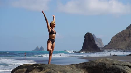 muscular build : Young girl in bikini balancing standing on one leg doing yoga standing on a rock by the ocean on a black sand beach
